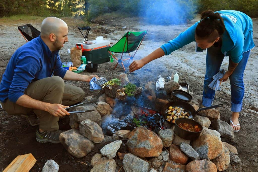 Couple cooking a Meal Over the Fire