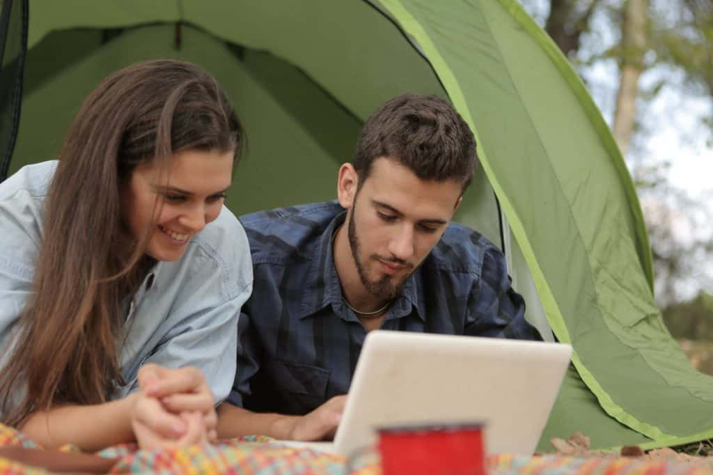 Young Couple Browsing on Laptop Laying in Tent